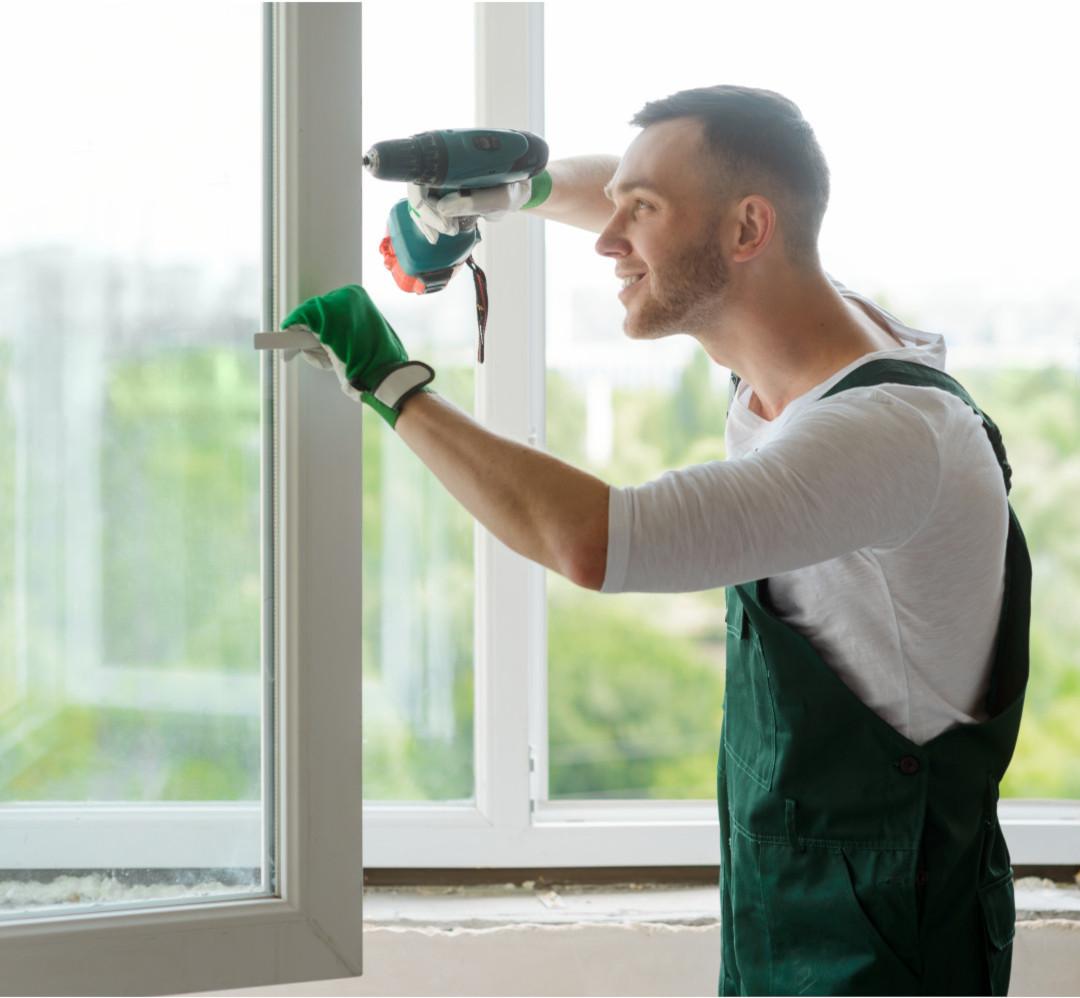 мастер ремонтирует окно